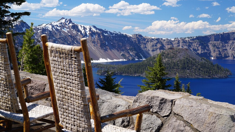 A view of Crater Lake with island in middle of water seen from the back of wicker wood rattan rocking chairs