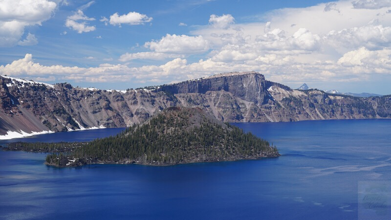 View of Crater Lake with island in the middle and blue skies dotted with puffy white clouds